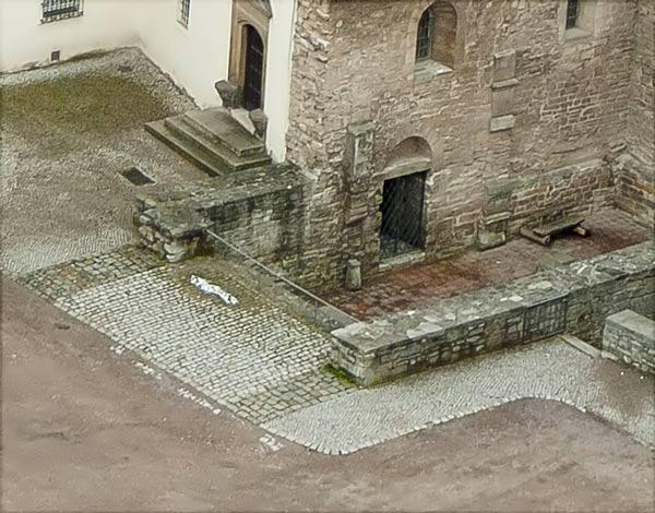 """Blick vom Bergfried auf die Burgkapelle, das Pflaster verdeutlicht den Verlauf der Fundamente. Im Vordergrund die durchlaufende Nordwand. Die Südwand (an der Treppe zum Portal des """"Krummen Hauses"""") ist nicht durchgängig, hier ist der Chor eingezogen."""